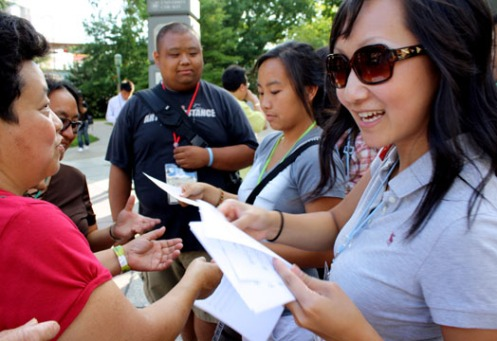 A participant at the Young Adult Catholics Conference aimed at Asian and Pacific peoples hands out singing sheets to other attendants on Friday.