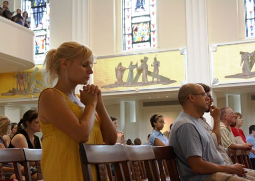 "Julie Hurt kneels in prayer during the service at Madonna della Strada Chapel. Theology on Tap, she said, was ""a great thing to do"" during the week."