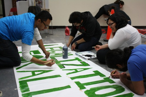 Tania and others paint banners for the march